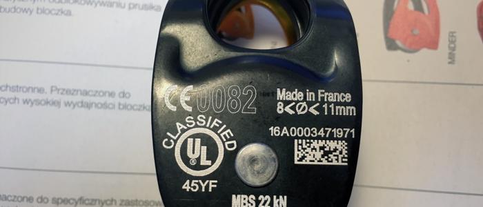 Bloczek pojedynczy firmy Petzl koloru czarnego na którym widnieją białe oznaczenia mówiące o wytrzymałości, certyfikacji, przeznaczeniu oraz numer indywidualny produktu.