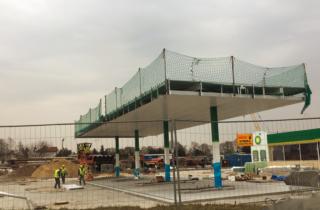Zdjęcie przedstawia stacje benzynowa w budowie na dachu której, zainstalowano zabezpieczenie w postaci siatką ochronnej uniemożliwiającej na upadek z wysokości pracownika.