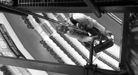 Alpinista przemysłowy wykonuje usługę konserwacji kamery przemysłowej na hali widowiskowej. W tle widac trybunę wraz z zamontowanymi krzesełkami