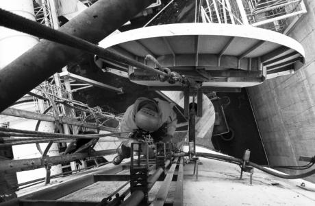 Pracownik wysokosciowy montuje na płaszczu komina antene radiową, która wyglądem przypomina antene satelitarną.