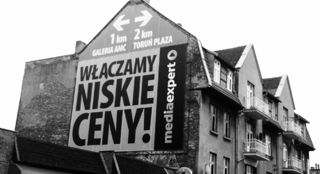 Zdjęcie przedstawia reklamę umieszczoną na bocznej ścianie budynku mieszkalnego. Skośny dach wymusił stworzenia reklamy, która wpisywał by się w kształt budynku.