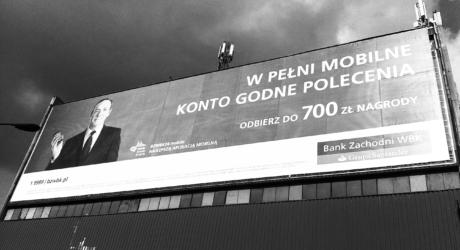 Widok reklamy wielkoformatowej zasłaniający połowe elewacji budynku. Reklama banku z udziałem amerykańskiej gwiazdy filmowej Kevinem Spacy.