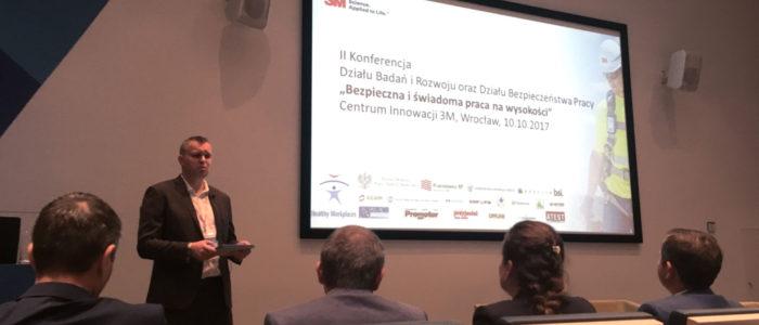 """Prelegent przedstawia gości II Konferencji Działu Badań i Rozwoju 3M """"Bezpieczna i świadoma praca na wysokości"""". W tle ekran prezentujący tematykę konferencji."""