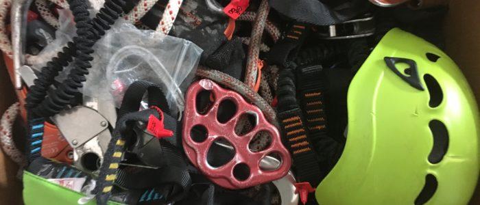 Karton pełen uszkodzonego sprzętu chroniącego przed upadkiem z wysokości, który służy do nauki i odnajdowania potencjalnych uszkodzeń.