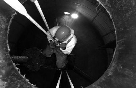 Pracownik przy pomocy technik linowych prowadzi prace konserwacyjne w komorze fermentacyjnej oczyszczalni ścieków. Pracownik do wnętrza zbiornika dostaje się przez mały otwór rewizyjny. Zjazd na linie umożliwia alpiniście przemysłowemu na dostęp do mieszadła.