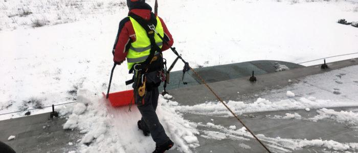 Pracownik ubrany w pełną uprząż, czerwony kask oraz kamizelkę odblaskową. Odśnieża dach budynku podpięty do systemu linowego chroniącego przed upadkiem.