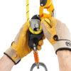 dłonie pracownika instalujące linę roboczą w przyrządzie zjazdowym RIG