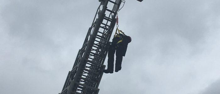 Ratownik wysokościowy uwalnia manekina wiszącego po upadku z wysokości.