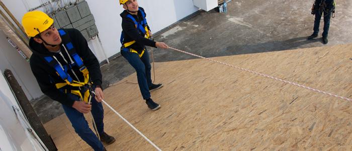 dwaj kursanci podczas szkolenia wysokościowego w Toruniu, szkolenie dotyczy bezpiecznej pracy na dachach płaskich i skośnych